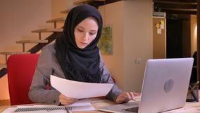 Closeup portrait of young beautiful muslim businesswoman comparing the data on the graph and on the laptop on the. Workplace indoors stock video