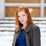 Closeup portrait of young beautiful redhead lady in blue dress and grey coat at winter outdoors Royalty Free Stock Image