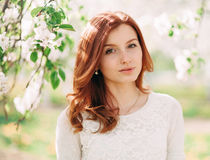 Closeup portrait of young beautiful redhead woman with an apple tree branch Stock Image