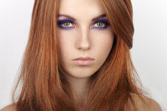 Closeup portrait of young beautiful redhead woman with gorgeous hair and violet eyes makeup Royalty Free Stock Photos