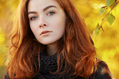 Closeup portrait of young beautiful redhead woman  in scarf and plaid jacket with autumn foliage background outdoors Royalty Free Stock Images