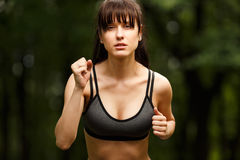 Closeup portrait of young beautiful woman brunette in motion. While Jogging outdoors. Concept of sport and healthy lifestyle Royalty Free Stock Photos
