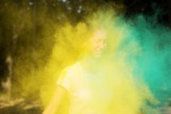 Closeup portrait of young blonde girl having fun with yellow paint at Holi festival of colors. Closeup portrait of young blonde woman having fun with yellow royalty free stock photography