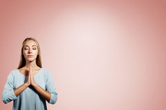 Closeup portrait of a young blonde woman praying. With closed eyes isolated on pink background Royalty Free Stock Images