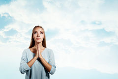 Closeup portrait of a young blonde woman praying. With closed eyes isolated on sky background Royalty Free Stock Photography