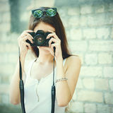 Closeup portrait of a young brunette woman posing with a film camera in a brick wall background Stock Photos