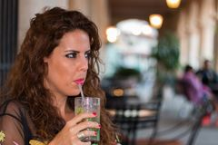 Closeup portrait of a young brunette woman on a terrace drinking a mojito stock photos