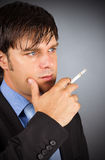 Closeup portrait of young businessman during a break smoking cig Stock Image