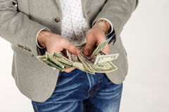 Closeup portrait of young businessman holding and counts money d Royalty Free Stock Image