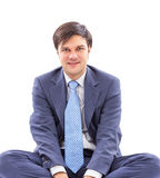 Closeup portrait of a young businessman sitting cross-legged Royalty Free Stock Image