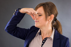 Closeup portrait of a young businesswoman holding her nose because of a bad smell. On gray royalty free stock images