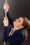 Closeup portrait of a young businesswoman trying to climb a rope Stock Image
