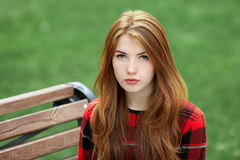 Closeup portrait of young calm redhead woman in red plaid jacket looking into camera with blurred green grass background Stock Photo