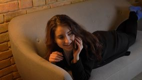 Closeup portrait of young caucasian brunette female lying on the couch and calling on the phone indoors in a cozy. Apartment royalty free stock photo