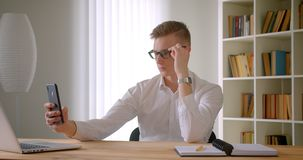 Closeup portrait of young caucasian businessman in glasses taking selfies on the phone posing in front of the camera. Indoors in the office stock video footage
