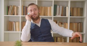 Closeup portrait of young caucasian businessman having a phone call in the office indoors with bookshelves on the stock footage