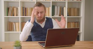 Closeup portrait of young caucasian businessman using the laptop and getting frustrated because of error in the office. Indoors with bookshelves on the stock video