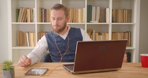 Closeup portrait of young caucasian businessman using the laptop in vibes listening to music with enjoyment in the. Office indoors with bookshelves on the stock video