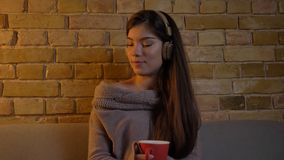 Closeup portrait of young caucasian female listening to music in headphones while sitting on the couch and enjoying a. Cup of warm tea in a cozy apartment stock photography