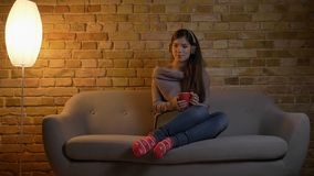 Closeup portrait of young caucasian female listening to music in headphones while sitting on the couch and holding a cup. Of tea indoors lookimng straight at stock images