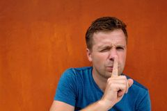 Closeup portrait of young caucasian man placing finger on lips as if to say, shh, be quiet. Silence on red background. Facial expression, human emotions signs Royalty Free Stock Photos