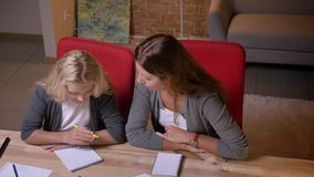 Closeup portrait of young caucasian mother teaching her small pretty girl and giving her a math task.  stock footage