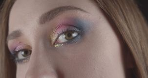 Closeup portrait of young caucasian short haired female face with eyes with pretty glitter makeup posing in front of the stock video footage