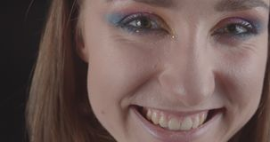 Closeup portrait of young charming caucasian short haired female face with cute glitter makeup looking at camera smiling stock video