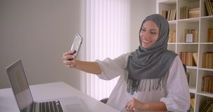 Closeup portrait of young cheerful muslim businesswoman in hijab taking selfies on phone posing sitting in front of. Laptop in office indoors stock video
