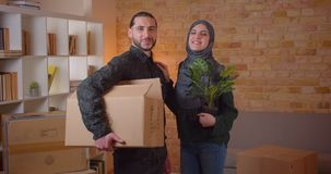 Closeup portrait of young cheerful muslim couple looking at camera standing in a newly bought apartment smiling happily stock footage