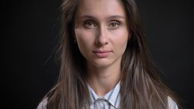 Closeup portrait of young cute caucasian female with brunette hair looking straight at camera with emotionless facial. Expression with isolated background royalty free stock images