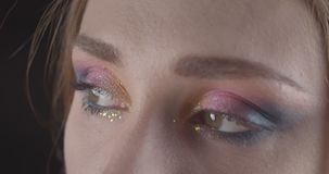 Closeup portrait of young cute caucasian short haired female face with eyes with glitter makeup posing in front of the stock footage