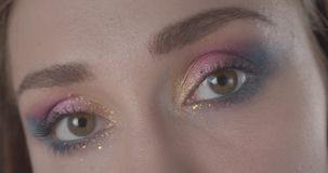 Closeup portrait of young cute caucasian short haired female face with glitter makeup looking at camera with background stock video footage
