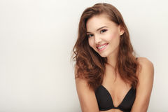Closeup portrait of young cute laughing brunette woman in black bra with adorable makeup posing bare shoulders on white studio bac Stock Images