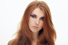 Closeup portrait of young cute redhead lady with violet smokey eyes makeup isolated. Closeup portrait of young cute redhead woman with violet smokey eyes makeup Royalty Free Stock Image