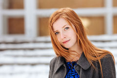 Closeup portrait of young cute redhead woman in blue dress and grey coat at winter outdoors Stock Photo