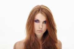 Closeup portrait of young cute smiling redhead lady with violet smokey eyes makeup isolated. Closeup portrait of young cute smiling redhead model with violet Stock Photo