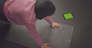 Closeup portrait of young determined athletic muslim female in hijab doing plank exercise using tracking app on phone. With green screen in gym stock footage