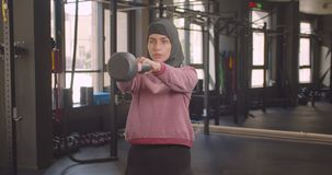 Closeup portrait of young determined athletic muslim female making squats with dumbbell in gym indoors.  stock footage