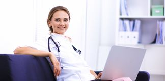 Closeup portrait of a young doctor sitting on the sofa Stock Images