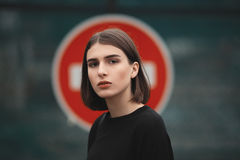 Closeup portrait of young elegant brunette hipster woman in black blouse against road  stop sign outdoors. Closeup portrait of young elegant brunette hipster Stock Photography