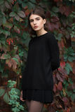 Closeup portrait of young elegant brunette hipster woman in black blouse and skirt against slight blurred ivy background Stock Images