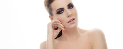 Closeup portrait of young elegant woman with dark fashion makeup touching her cheekbone posing with bare shoulders on white studio Stock Photo