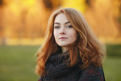 Closeup portrait of young emotional redhead woman  in scarf and plaid jacket with blurred autumn foliage background outdoors Royalty Free Stock Image