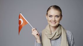 Female holding flag of Turkey. Closeup portrait of young female holding small flag of Turkey smiling at camera stock footage