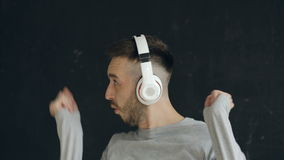 Closeup Portrait Of Young Funny Man Puts On Headphones And Crazy Dancing While Listen To Music On Black Background Caucasian Male