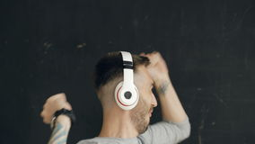 Closeup portrait of young funny man puts on headphones and crazy dancing while listen to music on black background stock footage
