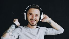 Closeup portrait of young funny man puts on headphones and crazy dancing while listen to music on black background Stock Photography