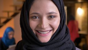 Closeup portrait of young funny muslim female office worker in black hijab looking at camera and laughing happily being stock footage