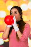 Closeup portrait of young girl clown mime blowing a balloon Royalty Free Stock Image